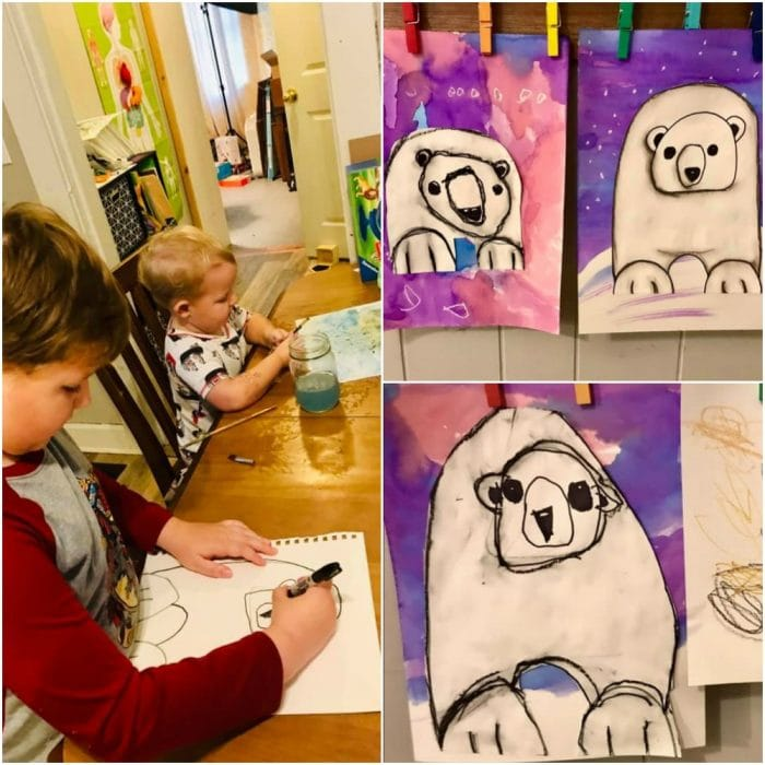 Two boys sitting at a table drawing. Finished art projects of polar bears.