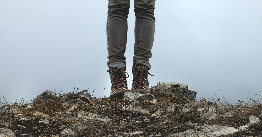 woman's legs with black jeans and hiking boots standing on top of rocks